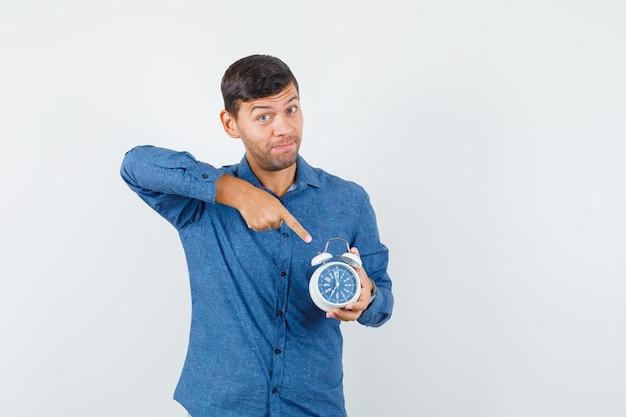 Jeune homme pointant sur réveil en vue de face de chemise bleue.