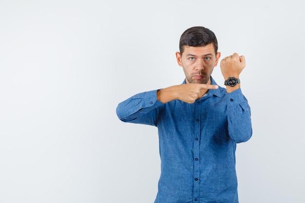 Jeune homme pointant sur sa montre en chemise bleue et semblant ponctuel. vue de face.