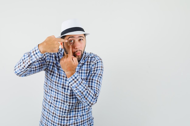 Jeune homme pointant sur sa paupière tirée par le doigt en chemise à carreaux