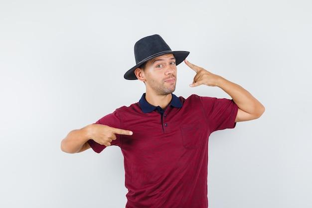 Jeune homme pointant sur son chapeau et sur le côté en t-shirt, chapeau et ayant l'air confiant. vue de face.
