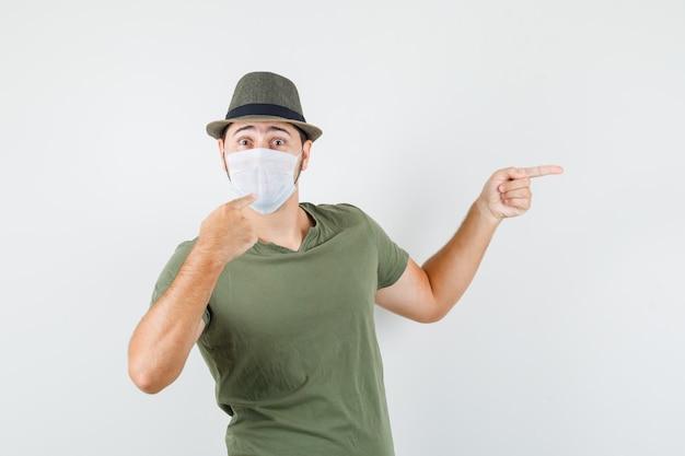 Jeune homme pointant sur son masque et sur le côté en t-shirt vert et vue de face de chapeau.