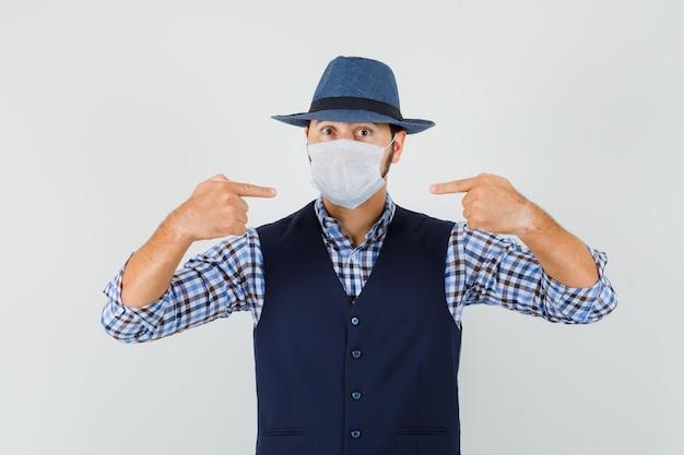Jeune homme pointant sur son masque médical en chemise, gilet, chapeau. vue de face.