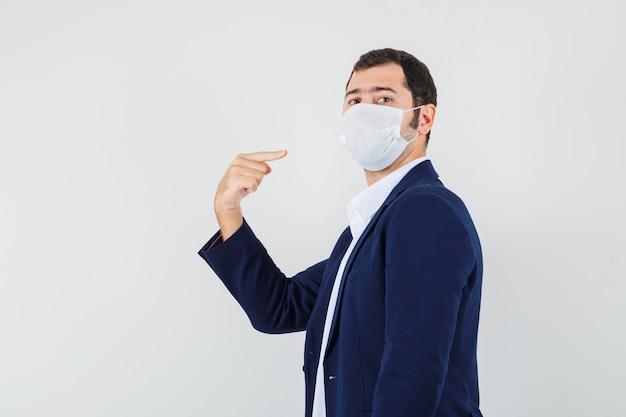 Jeune homme pointant sur son masque médical en chemise