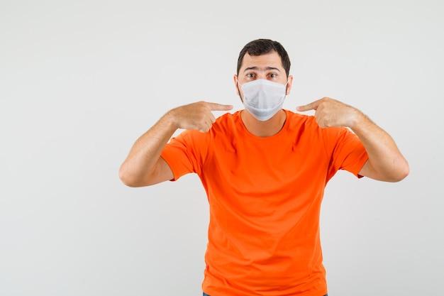 Jeune homme pointant sur son masque médical en t-shirt orange, vue de face.