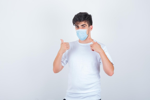 Jeune homme pointant sur son masque, montrant le pouce en t-shirt blanc et ayant l'air confiant