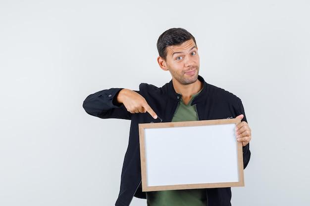 Jeune homme pointant sur un tableau blanc en t-shirt, veste et regardant joyeux, vue de face.