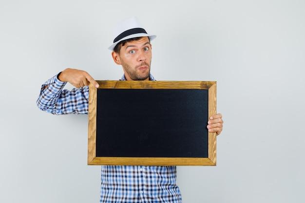 Jeune homme pointant sur tableau noir en chemise à carreaux