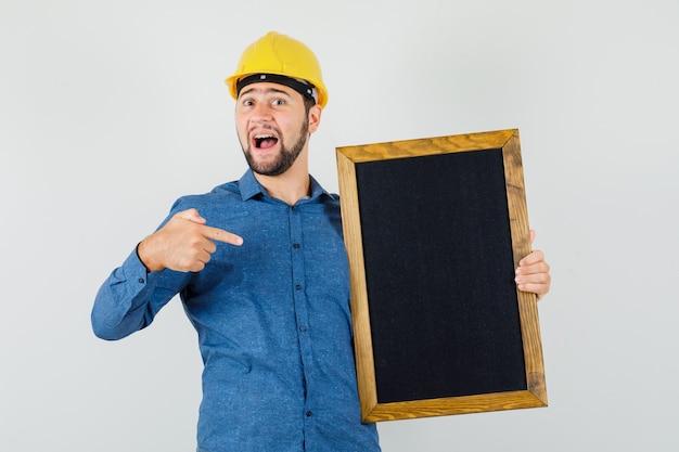 Jeune homme pointant sur tableau noir en chemise, casque et à l'optimiste, vue de face.