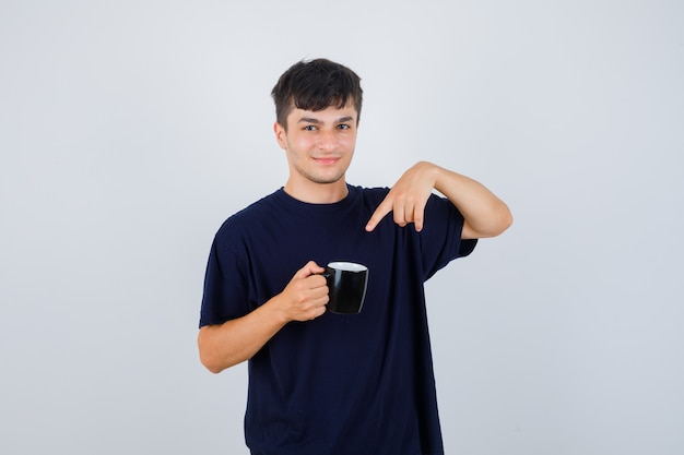 Jeune homme pointant sur une tasse de thé en t-shirt noir et à la vue de face, confiant.