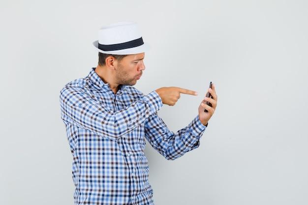 Jeune homme pointant sur téléphone mobile en chemise à carreaux