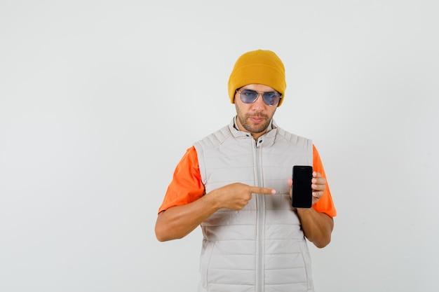 Jeune homme pointant sur téléphone mobile en t-shirt, veste, vue de face de chapeau.
