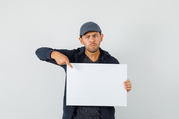 Jeune homme pointant sur une toile vierge en t-shirt