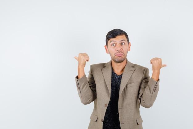 Jeune homme pointant vers l'arrière en veste marron grisâtre et à la perplexité. vue de face. espace libre pour votre texte