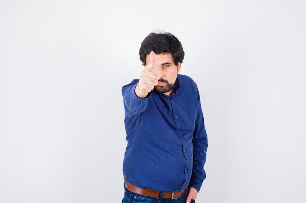 Jeune homme pointant vers l'avant en chemise, jeans et l'air confiant. .