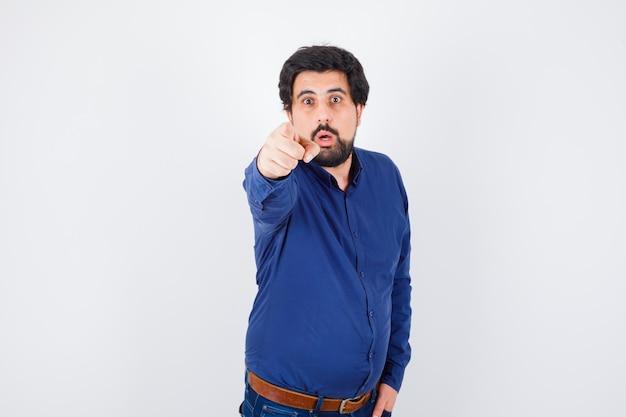 Jeune homme pointant vers l'avant en chemise, jeans et l'air étonné, vue de face.