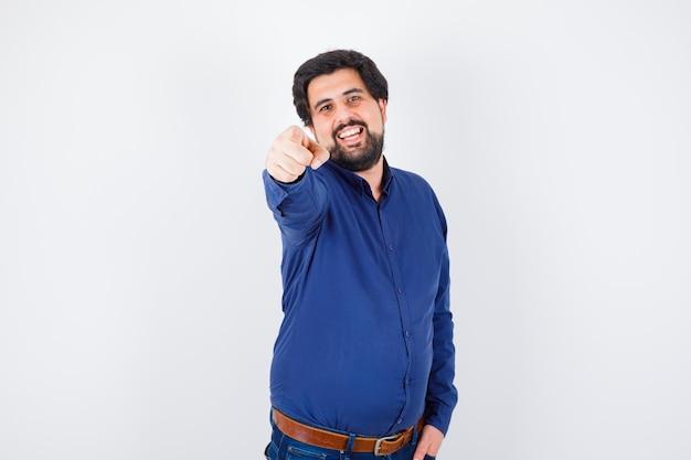 Jeune homme pointant vers l'avant en chemise, jeans et l'air heureux. vue de face.