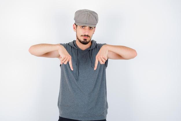 Jeune homme pointant vers le bas avec l'index en t-shirt gris et casquette et à grave