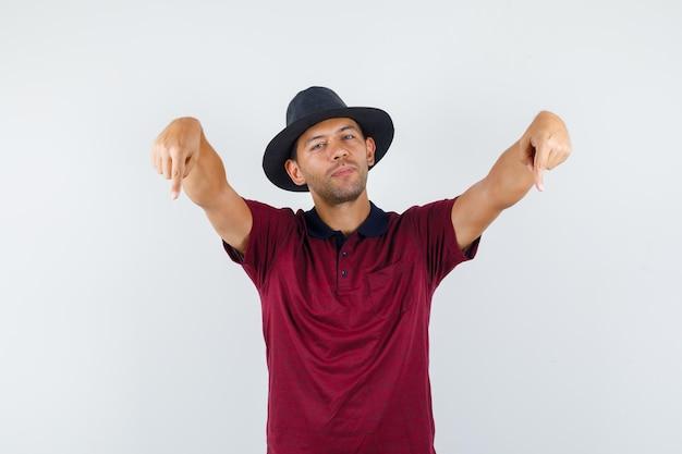 Jeune homme pointant vers le bas en t-shirt, chapeau et l'air confiant, vue de face.