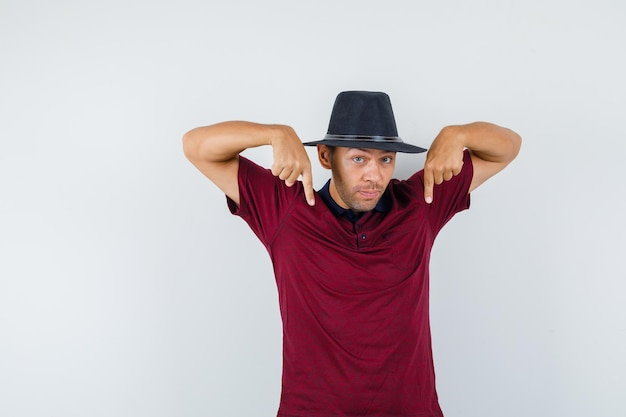 Jeune homme pointant vers le bas en t-shirt, chapeau et l'air curieux. vue de face.