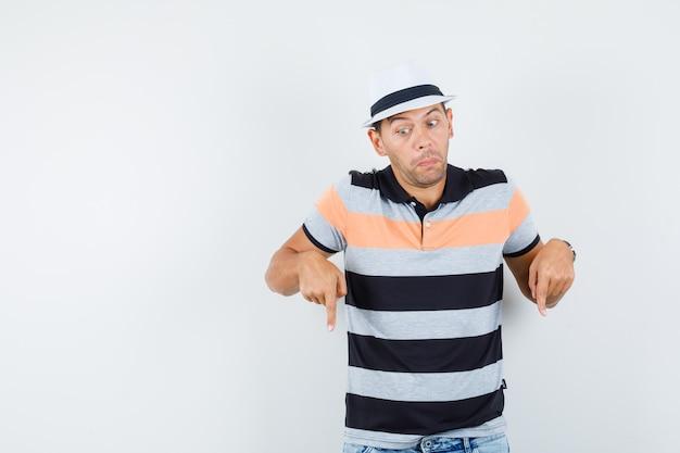 Jeune homme pointant vers le bas en t-shirt et chapeau, jeans et à l'ignorance