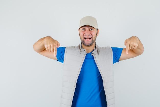 Jeune homme pointant vers le bas en t-shirt, veste, casquette et à la gaieté. vue de face.