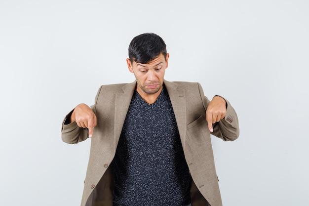 Jeune homme pointant vers le bas en veste marron grisâtre, chemise noire et l'air inquiet, vue de face. espace pour le texte