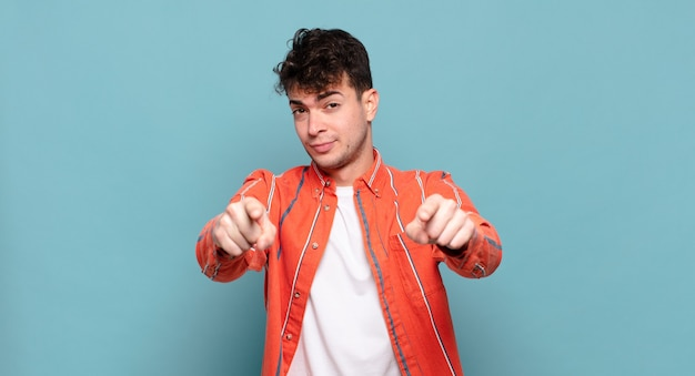Jeune homme pointant vers la caméra avec les deux doigts et une expression de colère, vous disant de faire votre devoir
