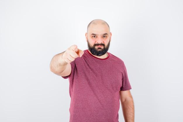 Jeune homme pointant vers la caméra avec l'index en t-shirt rose et regardant sérieux, vue de face.