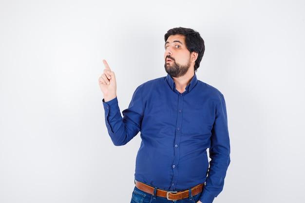 Jeune homme pointant vers le coin gauche en chemise, jeans et semblant drôle. vue de face.