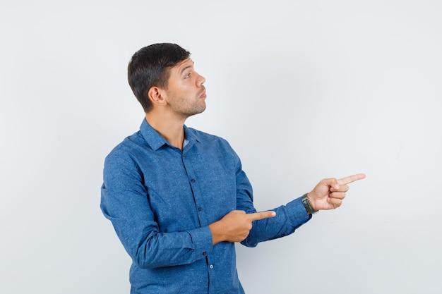 Jeune homme pointant vers le côté en chemise bleue et regardant concentré. vue de face.