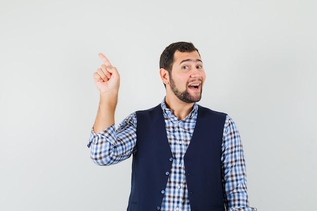 Jeune homme pointant vers le côté avec le doigt en chemise, gilet et à la joyeuse
