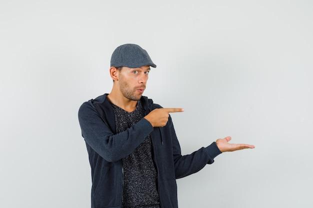 Jeune homme pointant vers le côté, étalant la paume de côté en t-shirt, veste, casquette et regardant curieux, vue de face.