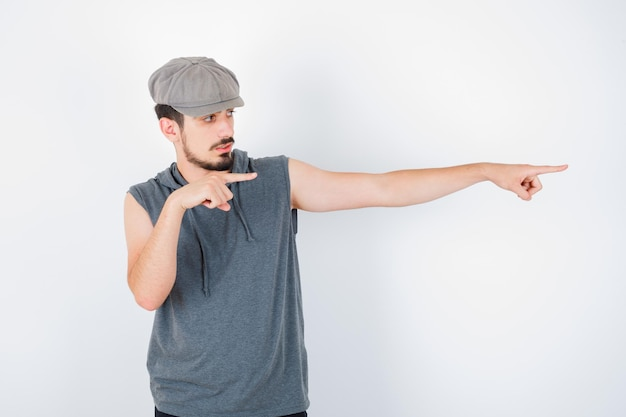 Jeune homme pointant vers la droite avec l'index en t-shirt gris et casquette et l'air sérieux