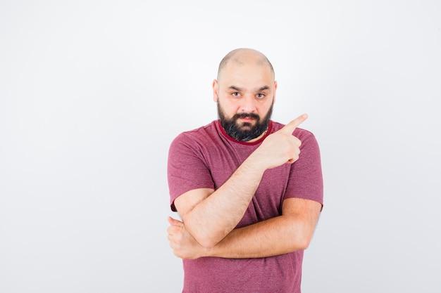 Jeune homme pointant vers la droite avec l'index en t-shirt rose et l'air sérieux. vue de face.