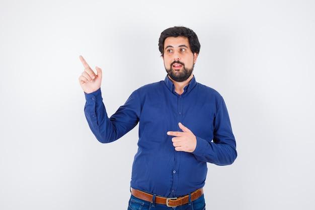 Jeune homme pointant vers l'extérieur en chemise, jeans et l'air heureux, vue de face.
