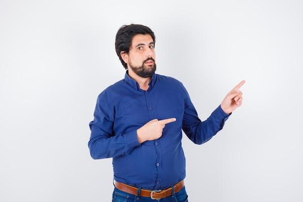 Jeune homme pointant vers l'extérieur en chemise, jeans et semblant mignon. vue de face.