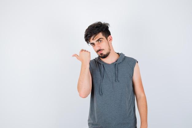 Jeune homme pointant vers la gauche en t-shirt gris et à la grave