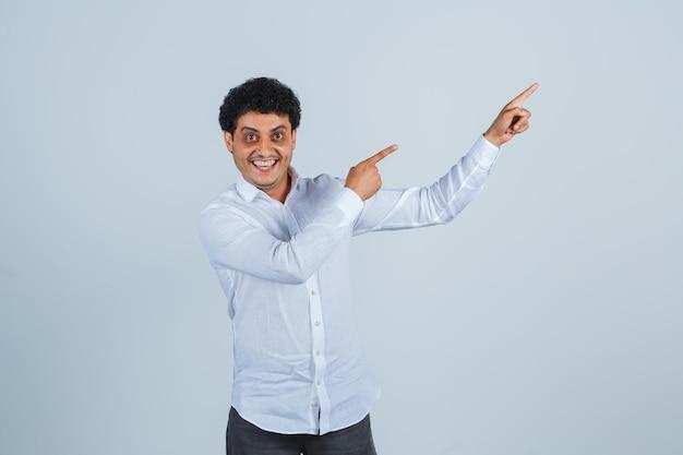 Jeune homme pointant vers le haut en chemise blanche, pantalon et l'air heureux. vue de face.