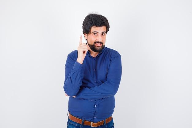 Jeune homme pointant vers le haut en chemise bleu royal et ayant l'air heureux. vue de face.
