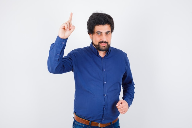 Jeune homme pointant vers le haut en chemise bleu royal et semblant attentif. vue de face.