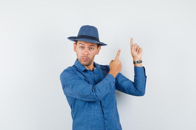 Jeune homme pointant vers le haut en chemise bleue, chapeau et l'air curieux, vue de face.