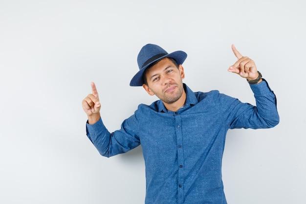 Jeune homme pointant vers le haut en chemise bleue, chapeau et à la cool. vue de face.