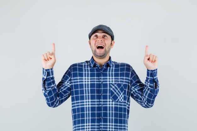 Jeune homme pointant vers le haut en chemise, casquette et à la reconnaissance. vue de face.
