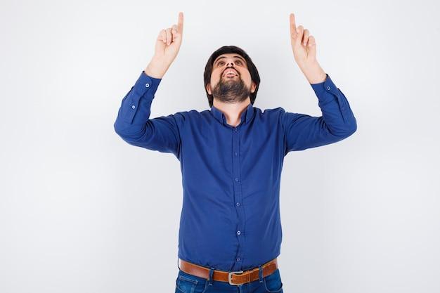 Jeune homme pointant vers le haut en chemise, jeans et semblant optimiste. vue de face.