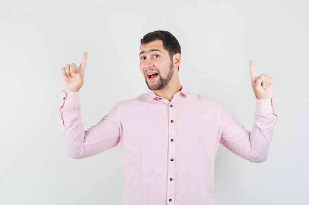 Jeune homme pointant vers le haut en chemise rose et à la joyeuse
