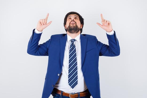 Jeune homme pointant vers le haut en chemise, veste, cravate et l'air curieux. vue de face.