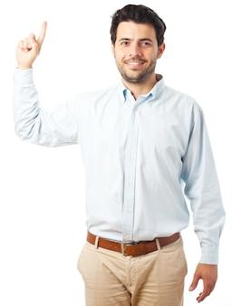 Jeune homme pointant vers le haut sur un fond blanc