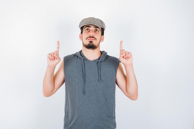 Jeune homme pointant vers le haut avec l'index en t-shirt gris et casquette et à grave