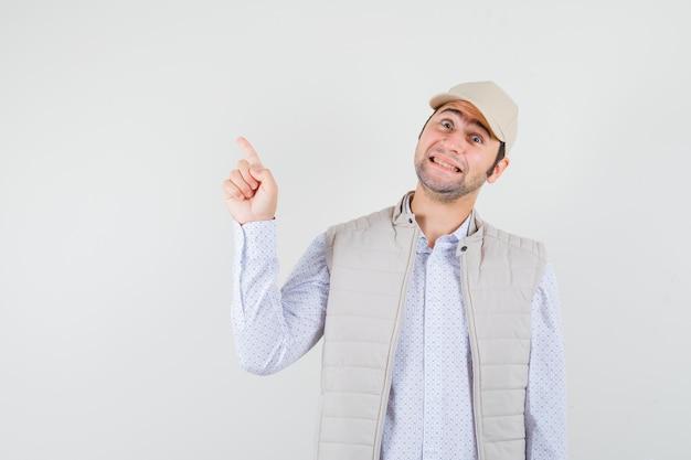 Jeune homme pointant vers le haut d'une main en veste beige et casquette et à la vue de face, heureux.
