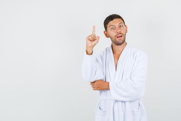 Jeune homme pointant vers le haut en peignoir blanc et à la smart, vue de face.